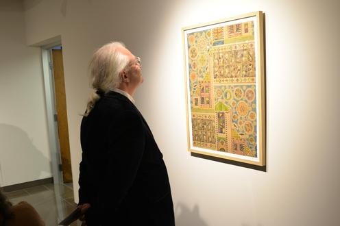 A man looking at the art work