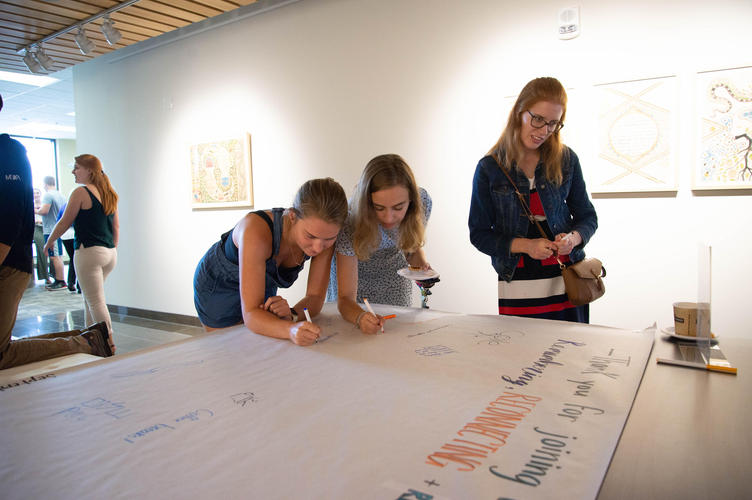 Guests sign memory board for Centre for Peace Advancement