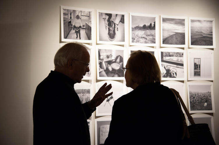 Guests chat in front of documentary photographs