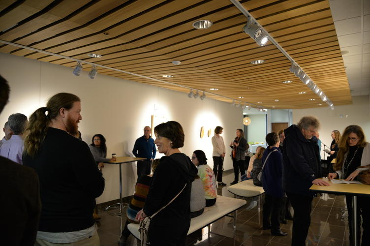 Guests conversing about the art pieces