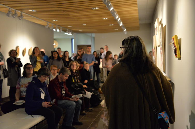 Catherine Dallaire speaking about the art pieces while guests listen attentively