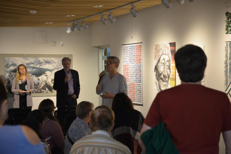 Heng-Gil Han showing speaking to guests about paintings