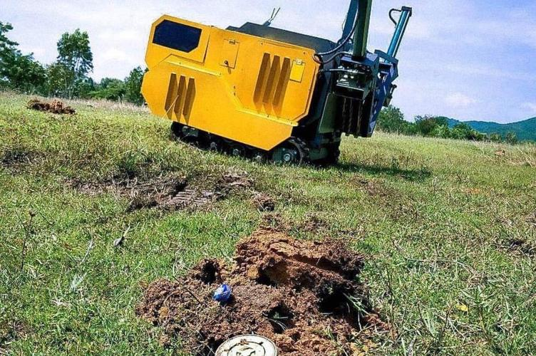 Excavator in field with landmine nearby
