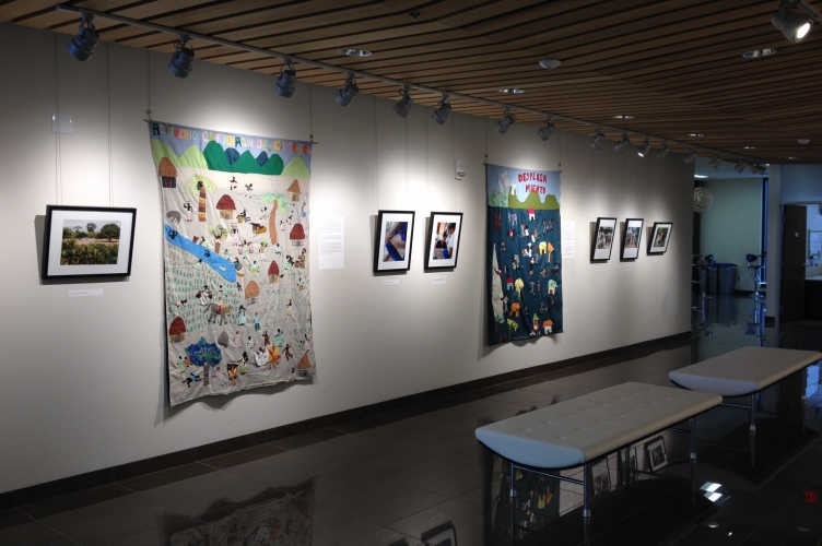 One wall of the exhibit with six photographs and two quilts