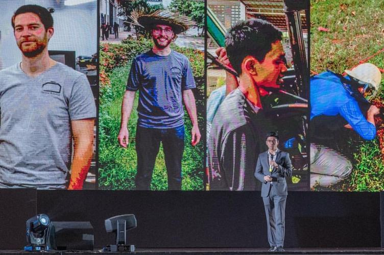 Richard on stage at Seedstars with images of Demine staff on screen
