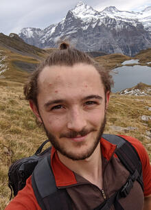 Neil wearing a rusty red collared shirt and grey backpack in front of a mountain