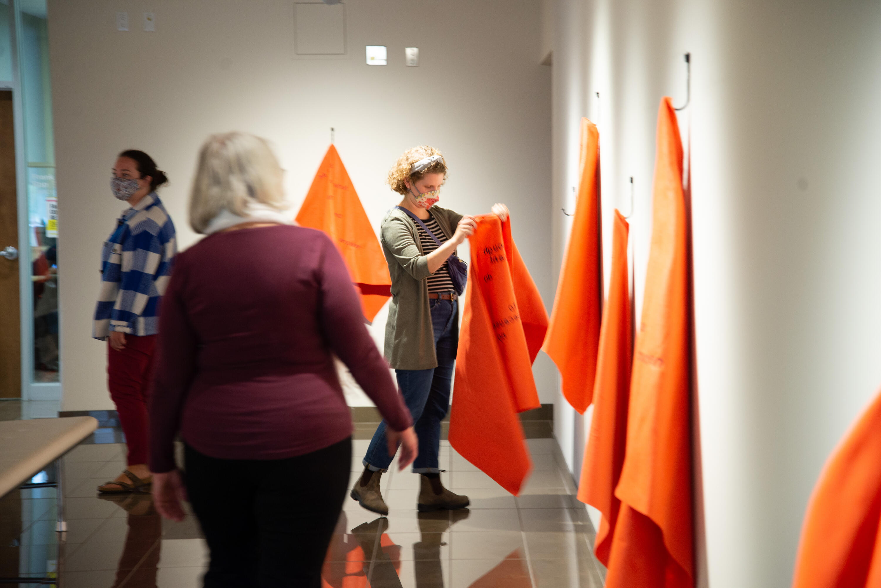 Amy Zavitz of Kindred Credit Union holds up an orange blanket at the Grebel Gallery
