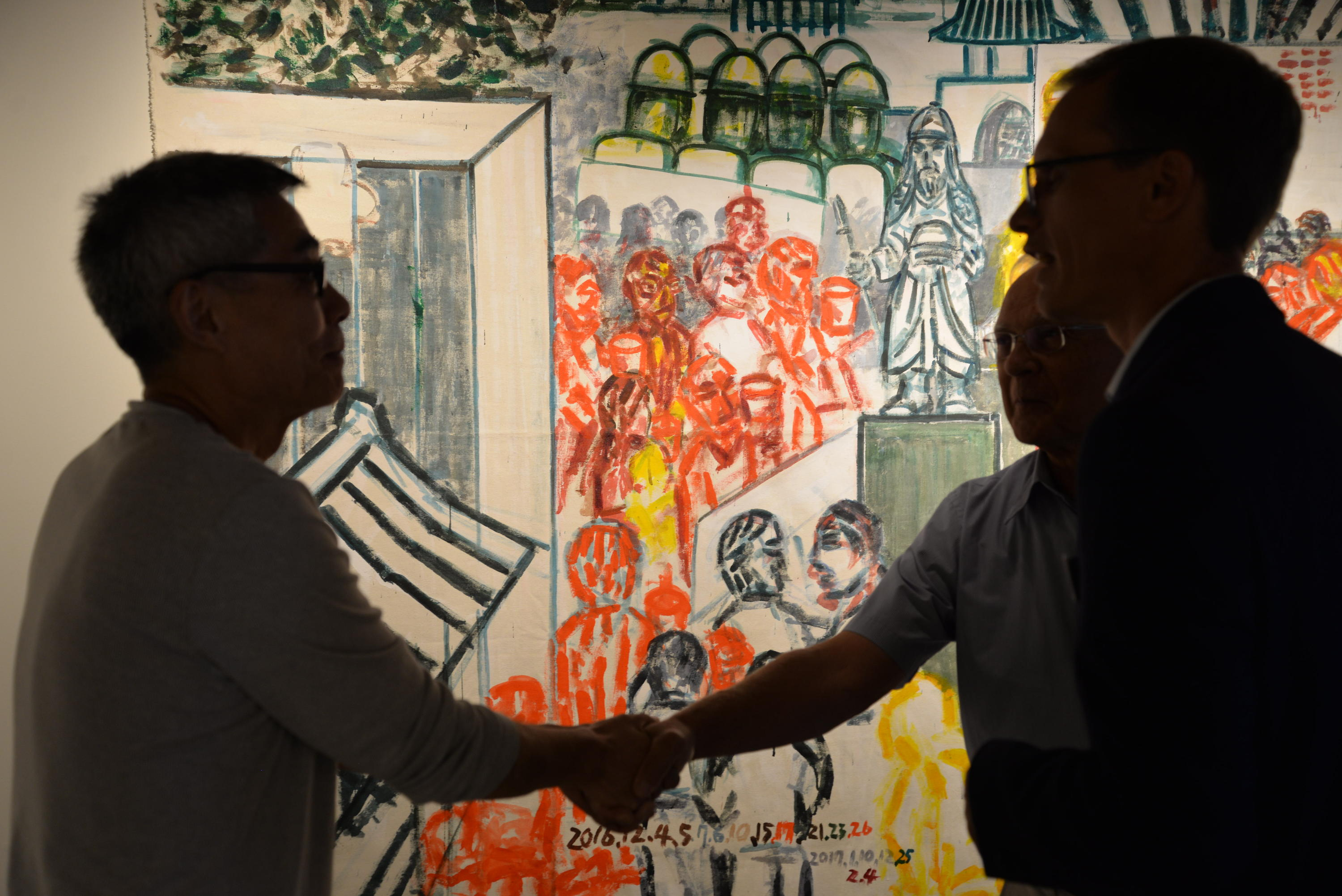 Two men shaking hands with art in background