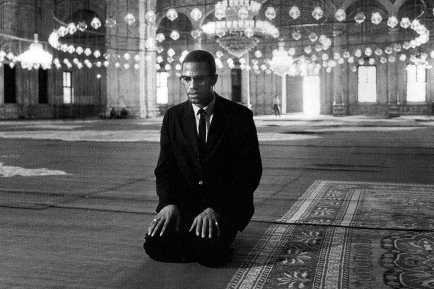 Malcolm X kneels on the ground while wearing a black suit during his 1964 pilgrimage to Mecca