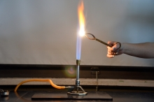 Bunsen burner and burning substance held in the flame by tongs.