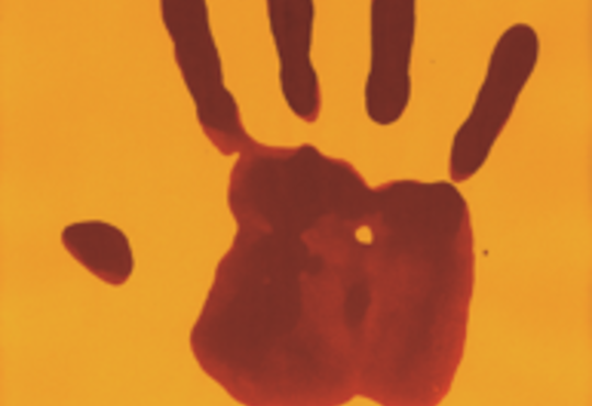 a red hand print on a mustard-coloured paper