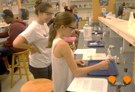 Students doing science experiments in front of their desks.
