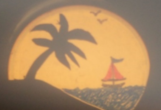 a sunset projected on a screen with a palm tree and a sailboat