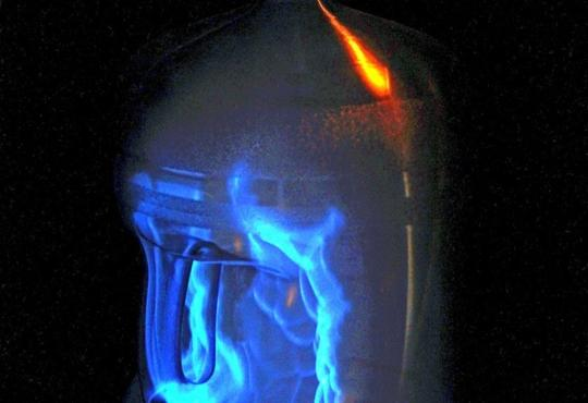 A bottle with blue flames inside and coming out of the top.