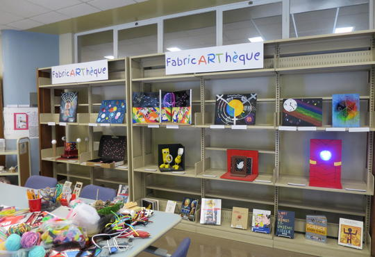 shelf in an artroom filled with art projects