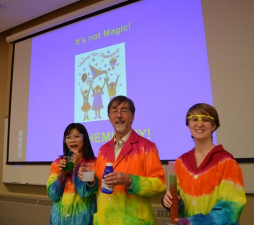 Three people wearing tie-dyed lab coats.