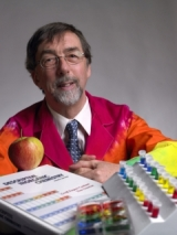 Geoff Rayner-Canham seated with periodic table of chemistry elements