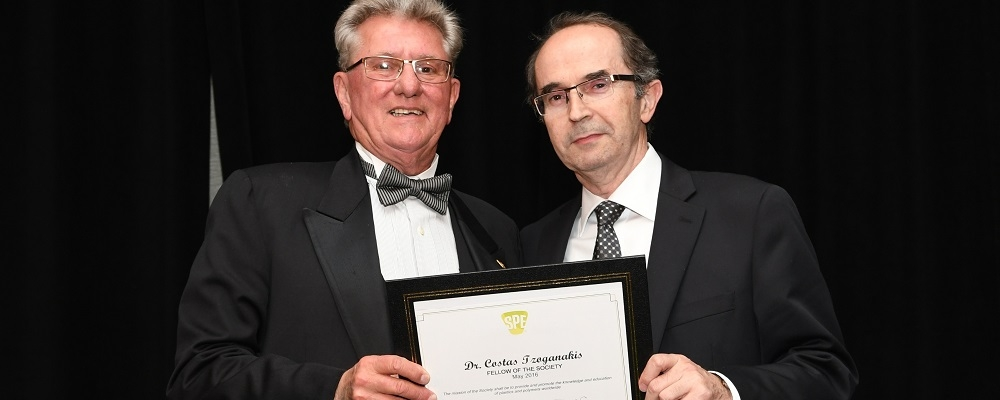 Costas Tzoganakis stands with society fellow holding award