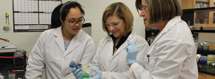 Three lab workers looking at a beaker