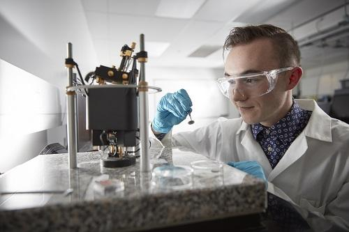 Student observing experiment in nanotechnology laboratory