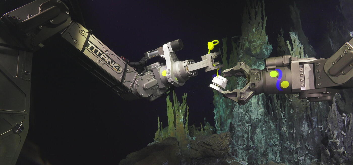 Remote Operating Vehicle arms holding a cube shaped sampling instrument. Background has blue hudrothermal vents covered in small