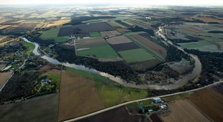 Aerial view of the Grand River and its surrounding fields.