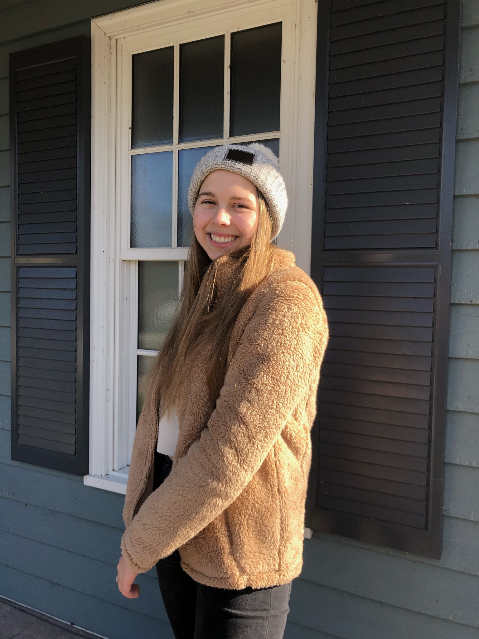 Natalia smiling infront of her house wearing a white hat and brown jacket