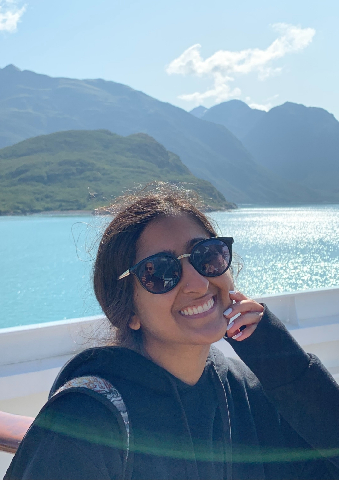 Celina smiling wearing sunglasses by a lake