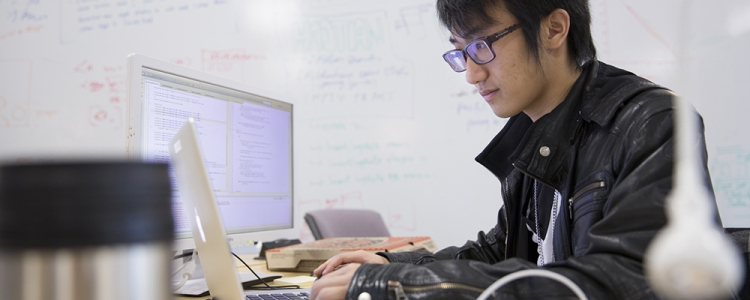 Student wearing leather jacket working on computer at a desk