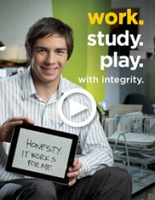 Image of workplace integirty with a co-op student holding a workplace integrity sign