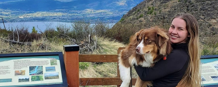 Miila standing while holding her dog in front of mountains