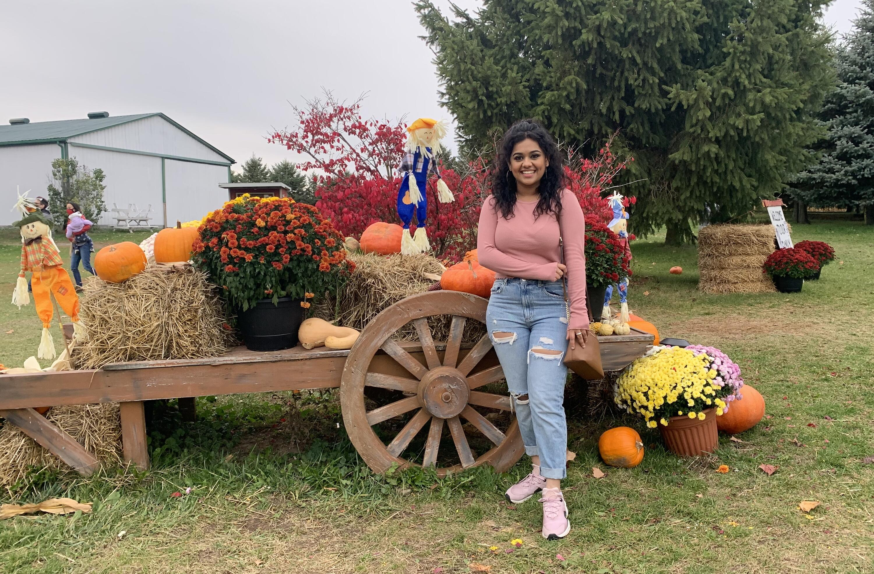 Nickie smiling with halloween decorations in a farm