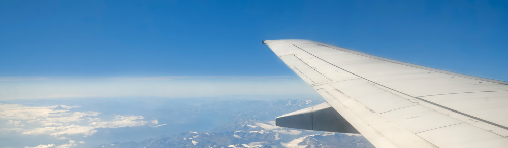 Picture of the view from inside an airplane looking at blue sky and an airplanes' wing