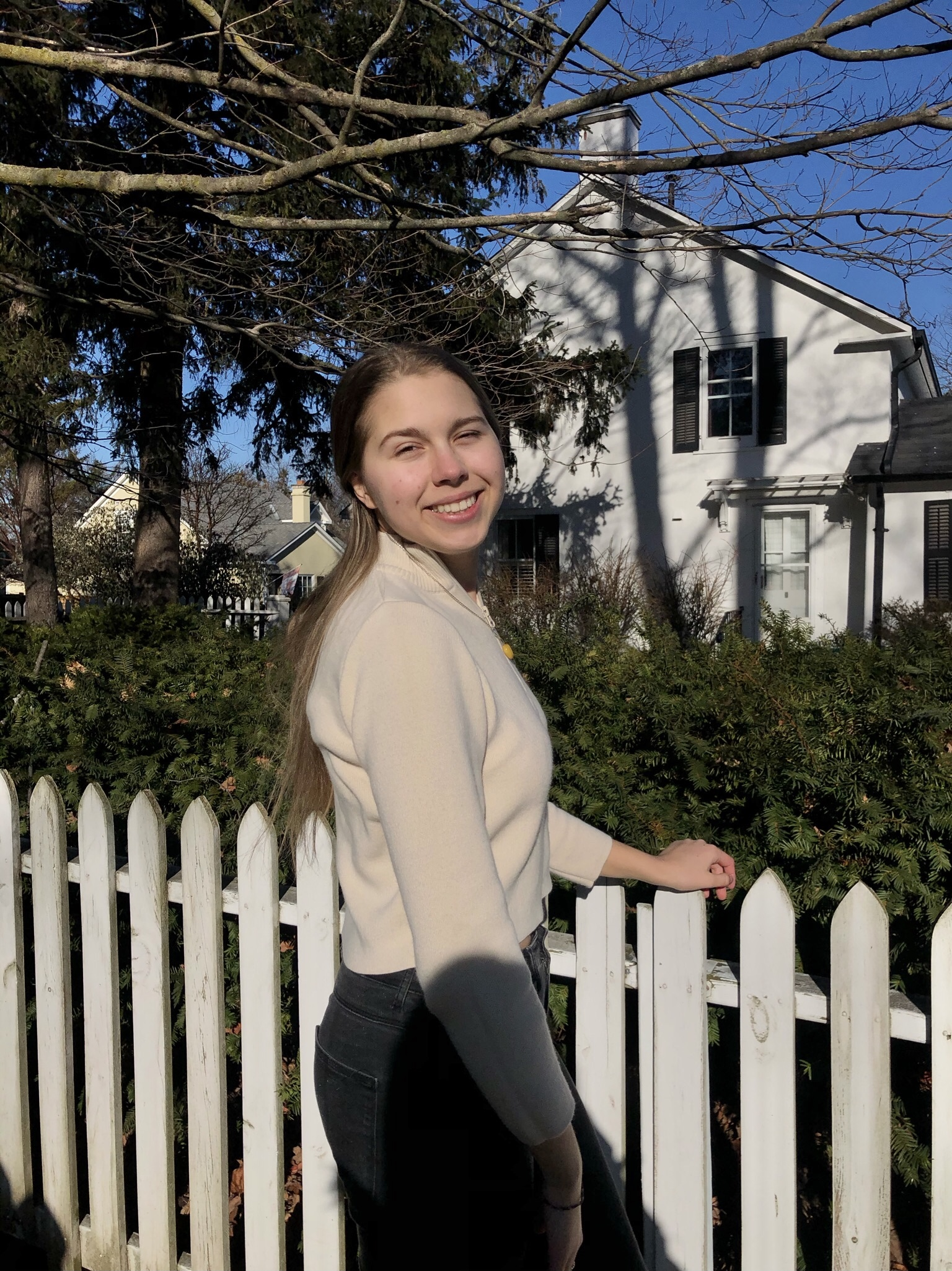 Natalia smiling infront of a white fence outside