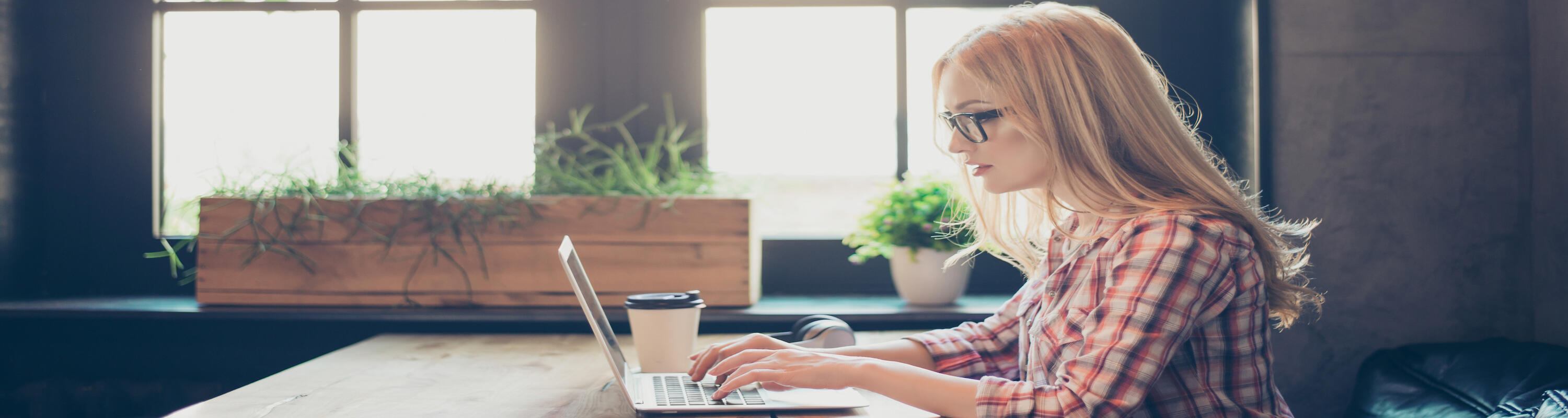 girl wearing glasses sitting at computer