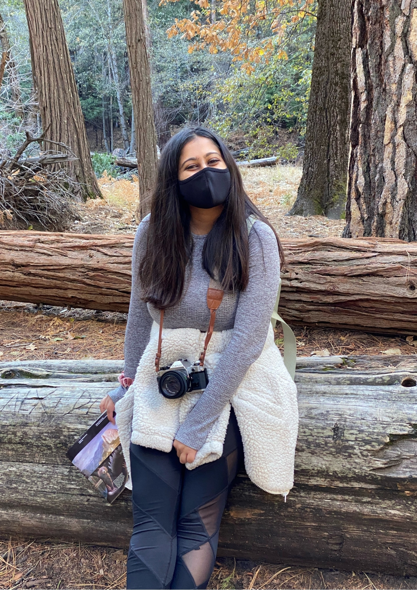 Celina wearing a mask in a park with her camera