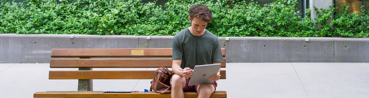 student on laptopn sitting on campus bench