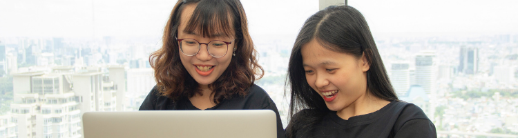 Two students looking at a laptop smiling