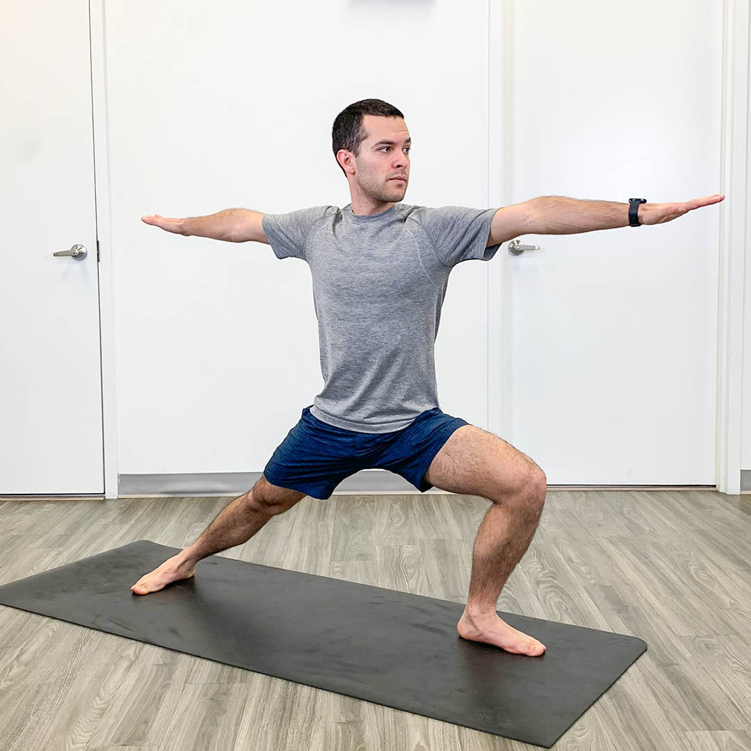 Jonah in a yoga pose standing on a yoga mat