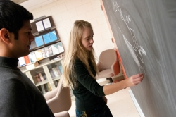 Students writing on a chalk board