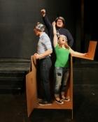 3 people playing in a cardboard box