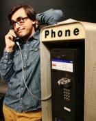 Man speaking on pay phone