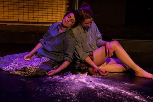 Girls on floor with dust and broken glass