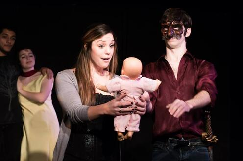 Commedia dell'arte characters hold baby