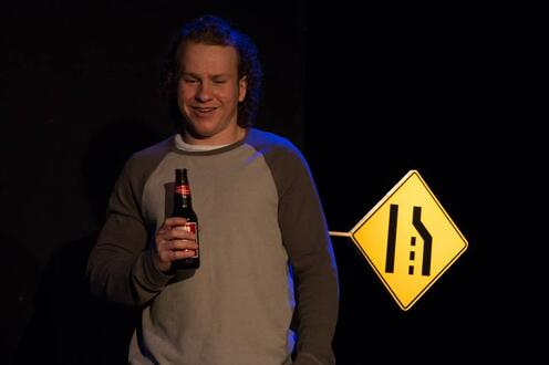 Man holds beer bottle with road sign behind him