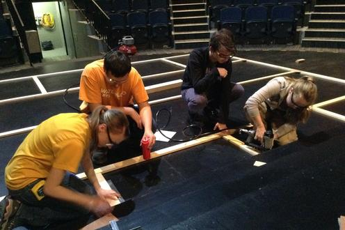The carpentry crew puts the set walls together