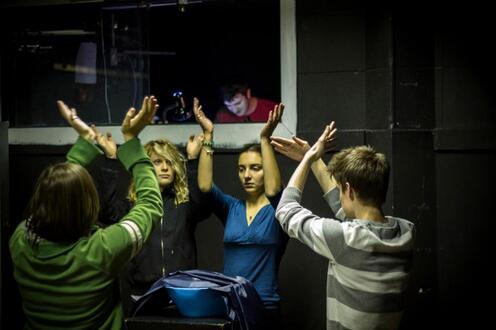 Actors wave hands around bowl