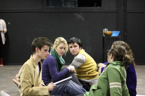 Actors sit on floor