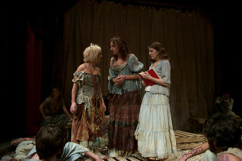 Three woman standing in dresses on stage