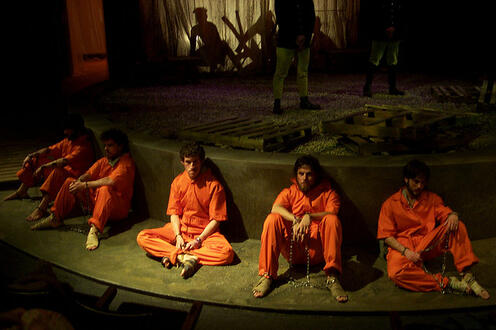 Group of men sitting in prison uniforms